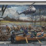 mural of a plane and people in a canoe escaping a flood