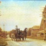 painted mural on brick wall showing a horse carriage and people dressed on old clothes