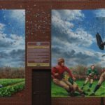 mural of a military plane dropping confetti over a farmland and a football match