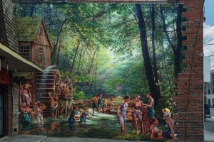 brick wall mural of people swimming in forested area