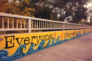 mural on railing on bridge saying everyone. everywhere