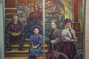mural of two men, two women and a child looking towards the viewer