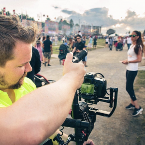man holding a camera on gimbal filming a lively event