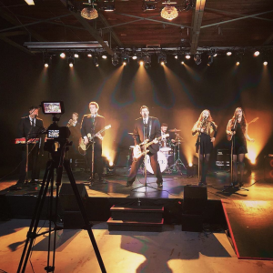 camera filming a band performing on stage
