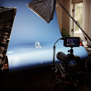camera filming a glass of water on blue background